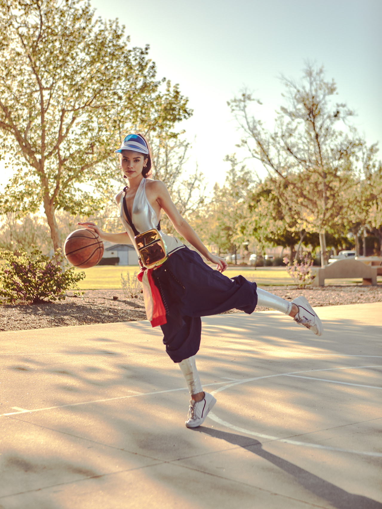 Model Gracie Phillips plays basketball and models a silver bodysuit and a retro red, white, and blue athletic jumpsuit from Urban Outfitters along with a metallic backpack and shoes by Adidas for a sporty summer fashion editorial by Patrick Patton Photography.