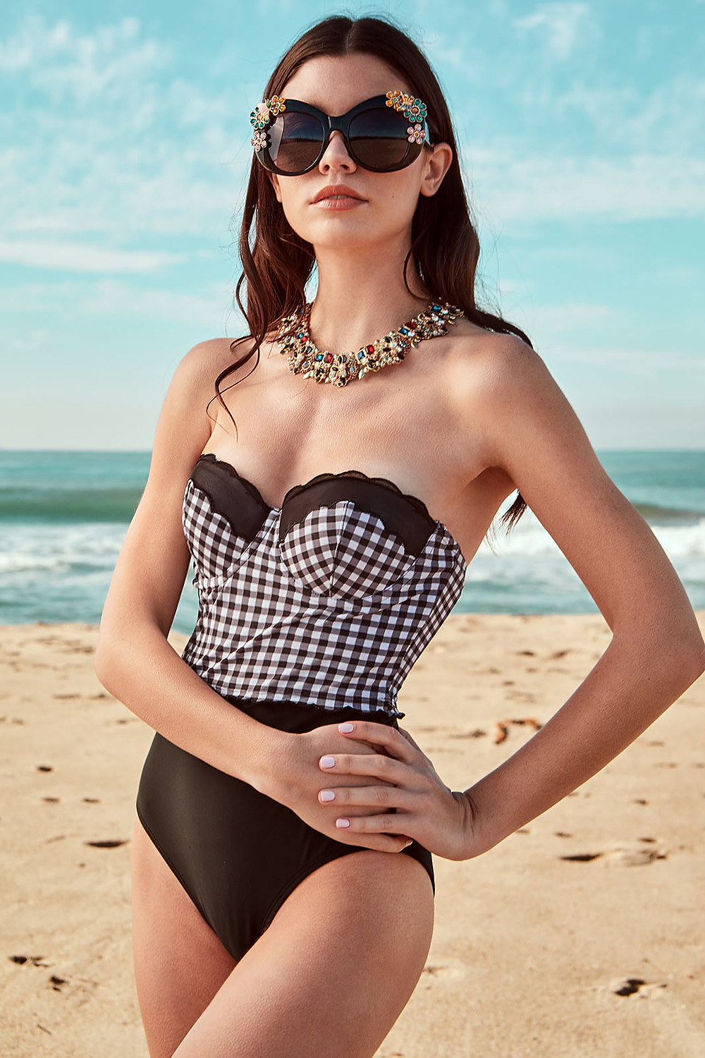 Swimwear model Gracie Phillips models a black and white gingham one piece swimsui by Betsy Johnson
