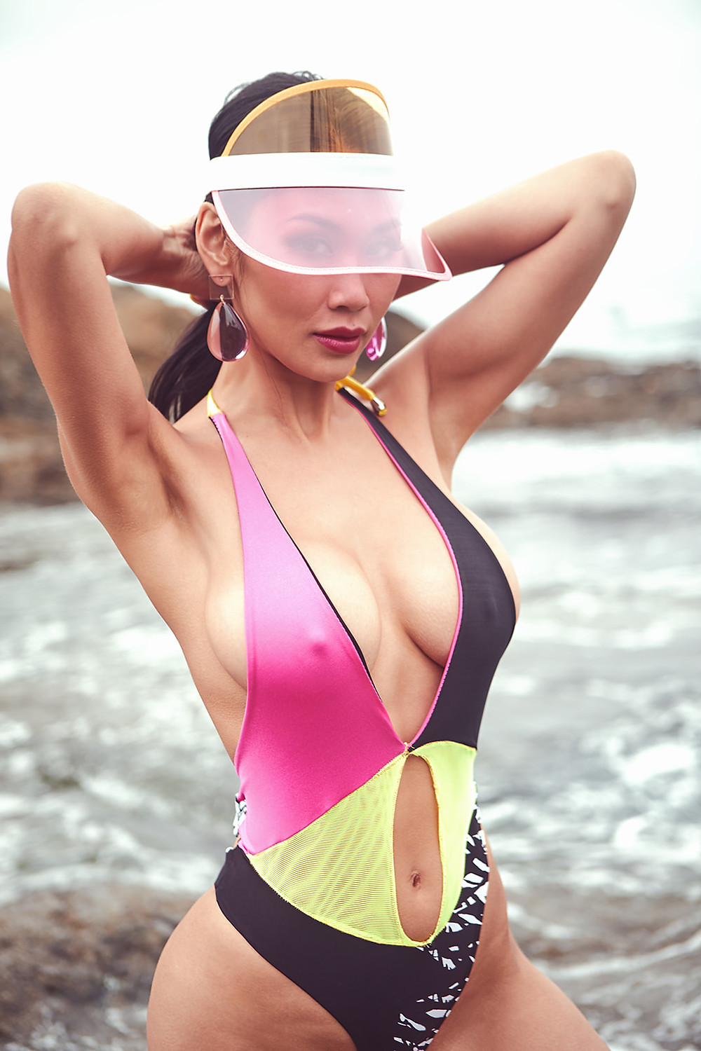 Model and fashion influencer Claire Reine Godard poses in a pink, yellow mesh, black, and zebra print bikini on the sand in Laguna Beach for a swimwear editorial shot by Patrick Patton for New Face Magazine July 2019.