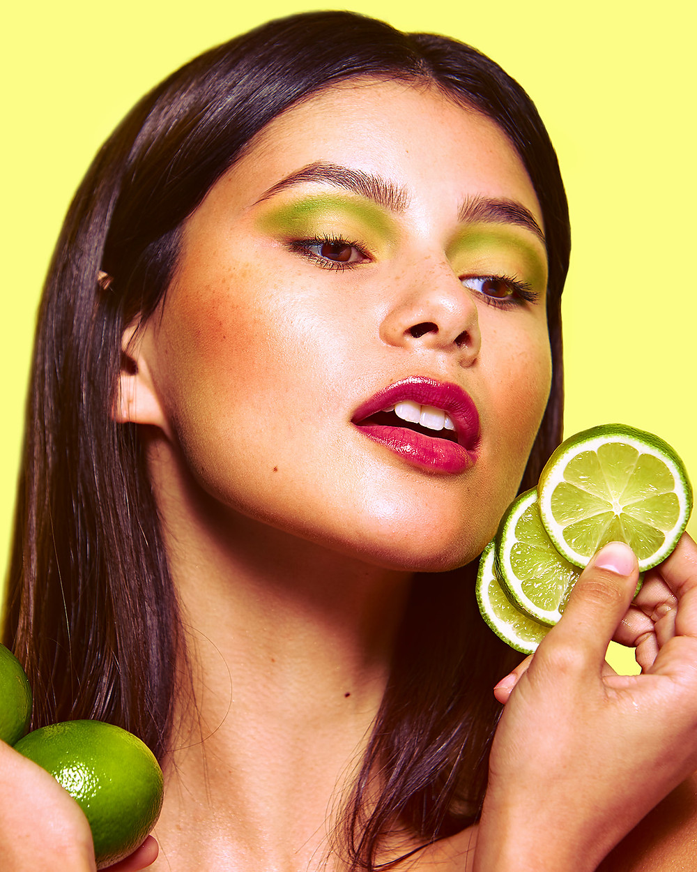 Model Genevieve van Dam holds sliced and whole limes in a fruit-inspired beauty editorial photo shoot published in New Face Fashion Magazine and photographed by commercial and fashion photographer Patrick Patton.