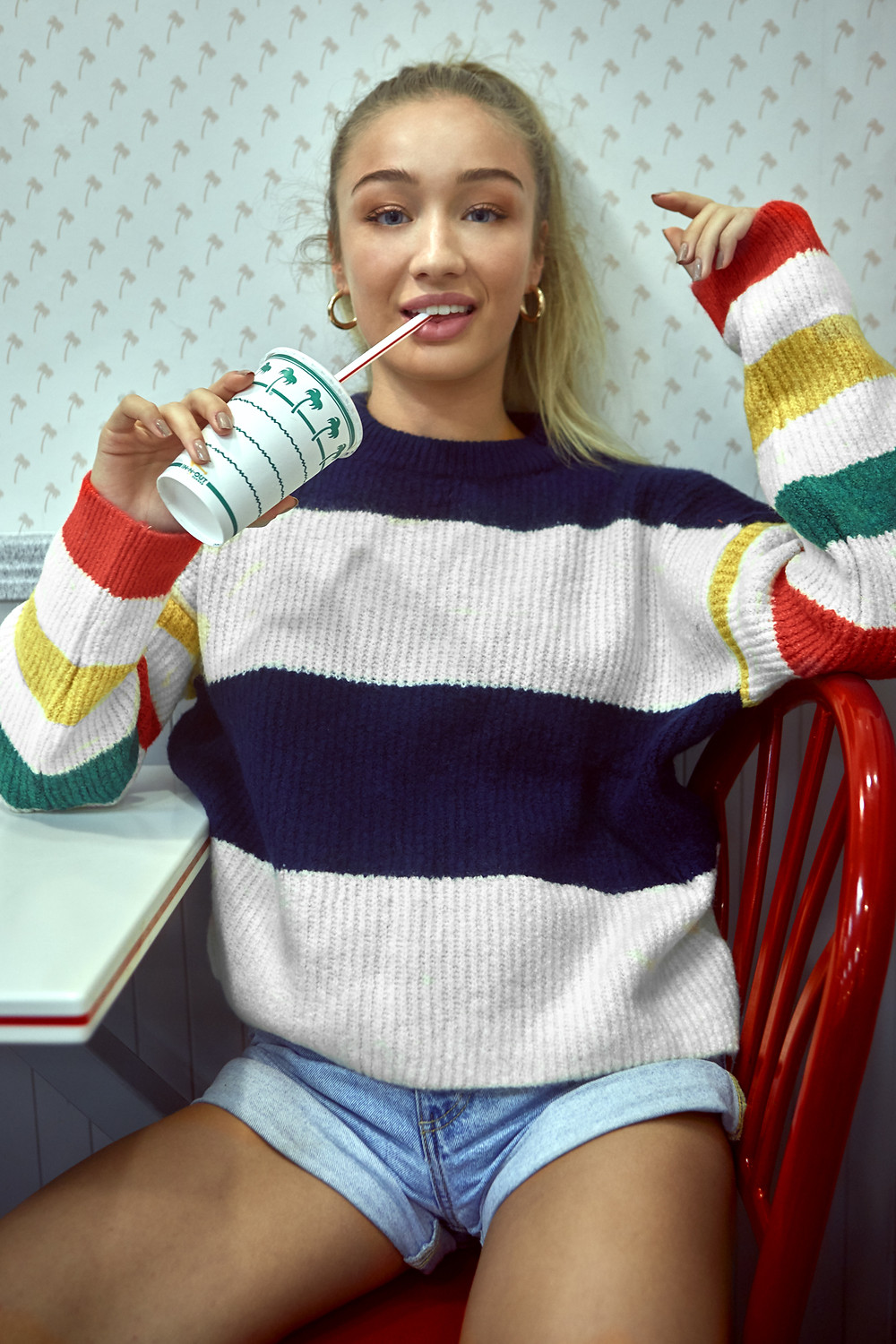 Manchester model Bethan Sowerby tries In N Out Burger for the first time.  Photographed by Patrick Patton, she wears denim shorts and a Truly Madly Deeply Caroline Stripe Sweater from Urban Outfitters while sipping on a strawberry milkshake.