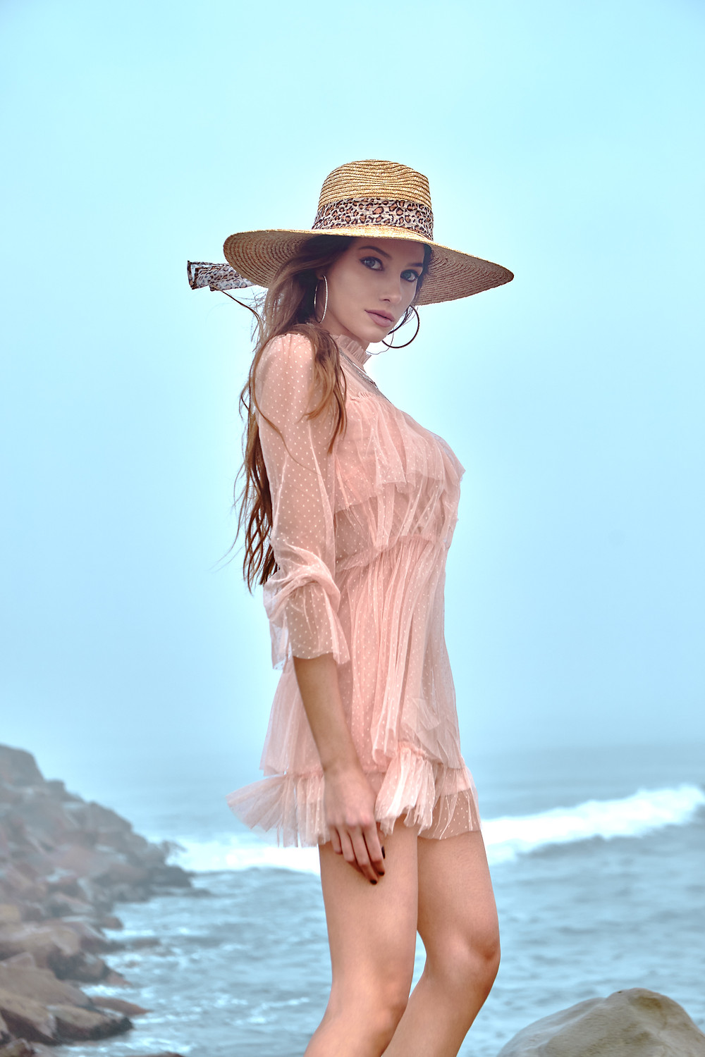 Fashion portrait of model Sofija Stojkovic at Aston Models in Los Angeles, California wearing a pink beach dress, large hoop earrings, and a straw hat with a leopard sash.
