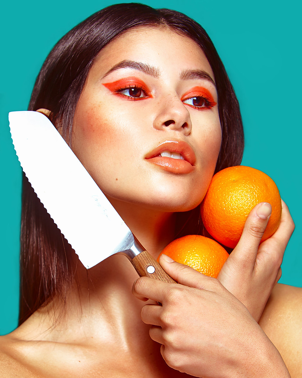 Model Genevieve van Dam holds oranges and a knife in a fruit-inspired beauty editorial photo shoot published in New Face Fashion Magazine and photographed by commercial and fashion photographer Patrick Patton.