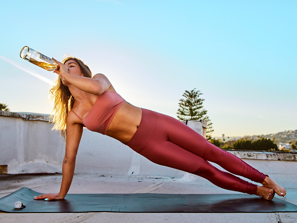 """Tori Deal of SuiHeart Club doing """"Woga"""" (Wine + Yoga) in pink yoga pants and bra on a rooftop in Downtown Los Angeles while drinking a bottle of Rosé Wine.  Photography by Patrick Patton."""