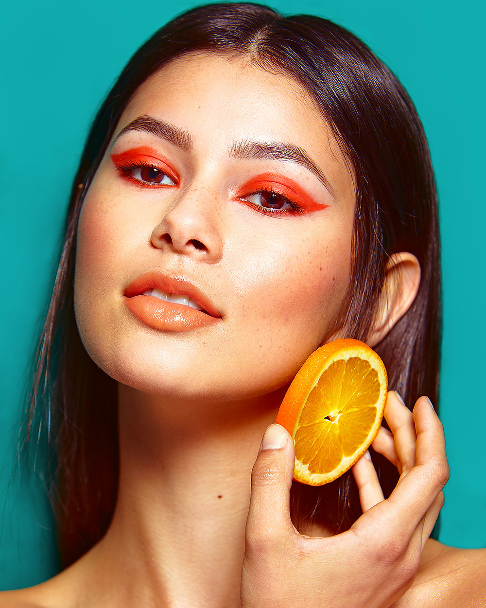 "Model Genevieve van Dam holds sliced orange ""earrings"" in a fruit-inspired beauty editorial photo shoot published in New Face Fashion Magazine and photographed by commercial and fashion photographer Patrick Patton."