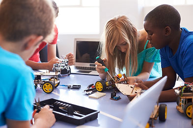 A class tinkering with a drone.