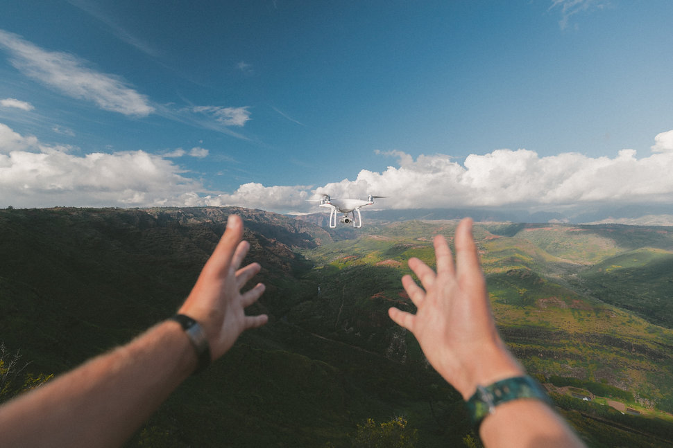 Man reaching out to a flying drone.