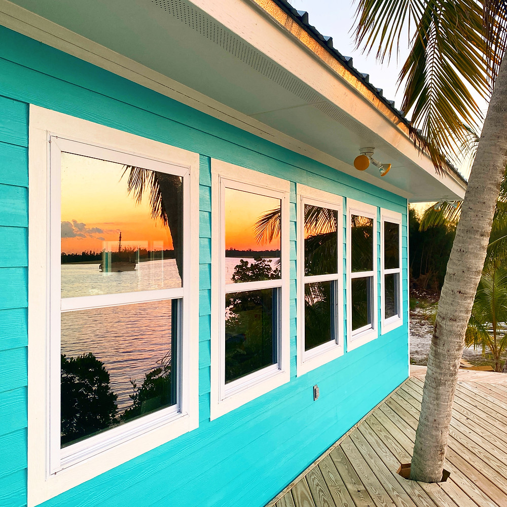 Windows reflecting a boat against a beautiful island sunset
