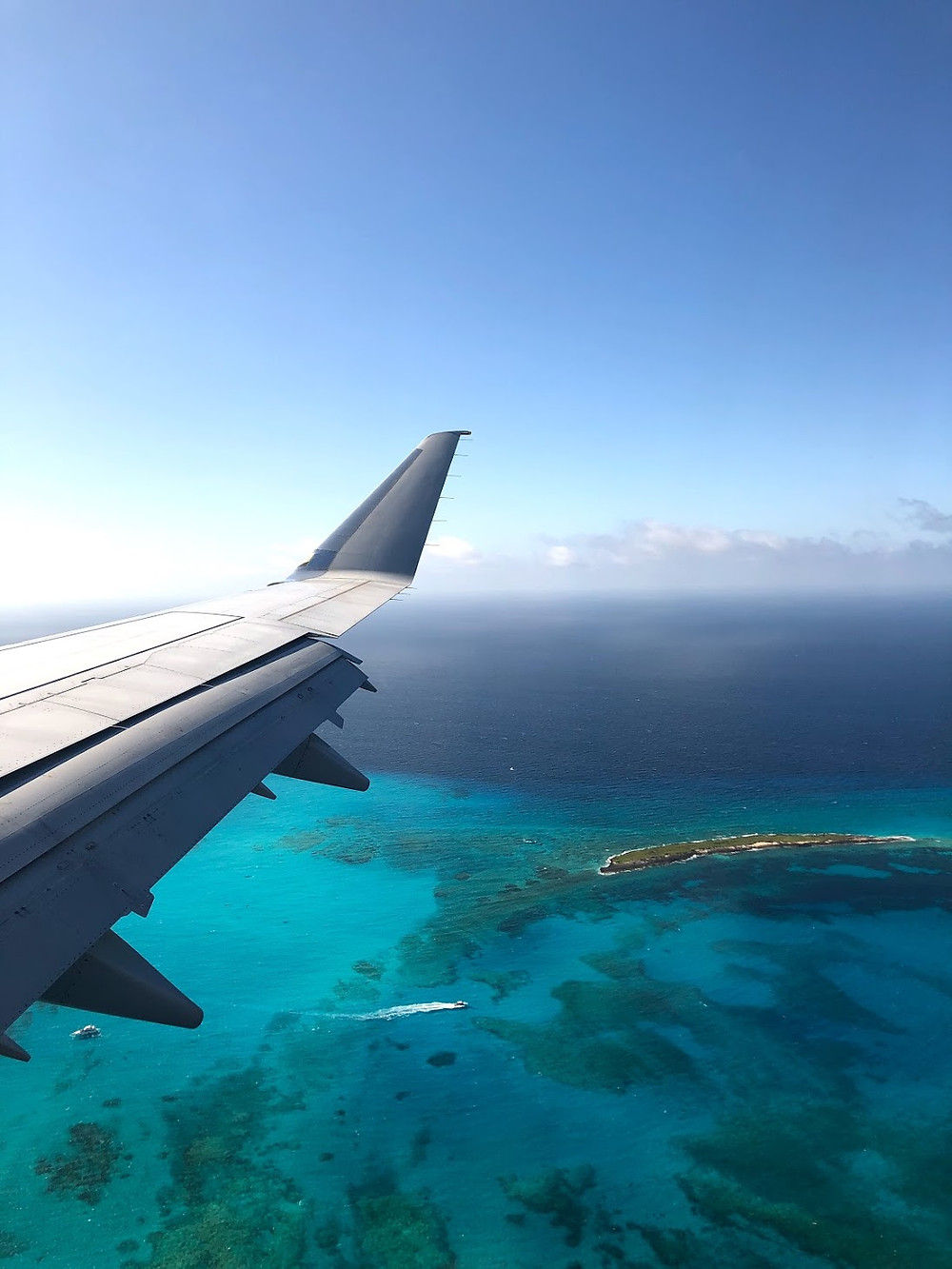 partial wing of airplane flying over turquoise ocean