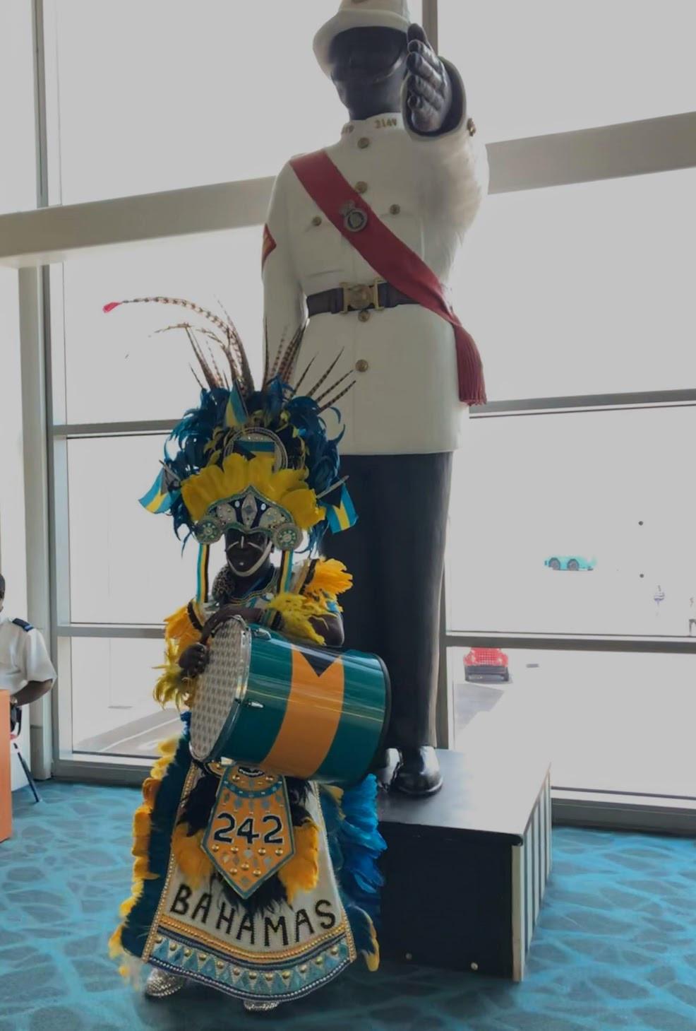 Junkanoo performer in front of statue of Bahamas police