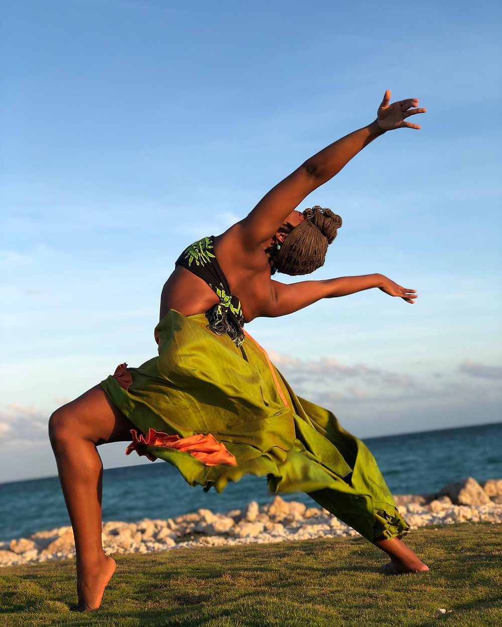 Bahamian woman in a dance pose with ocean in the background