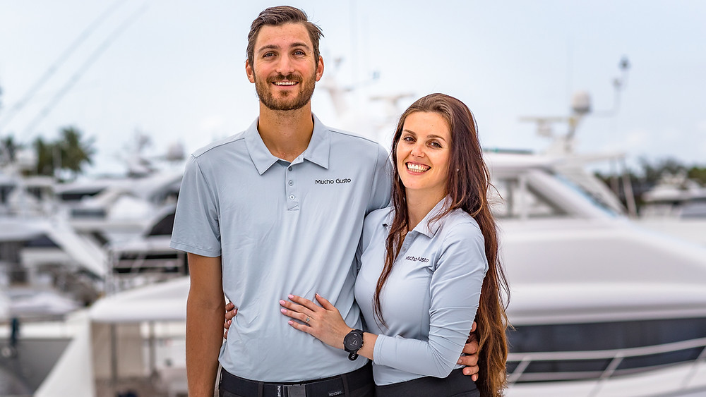 Caucasian man and woman with yacht in background
