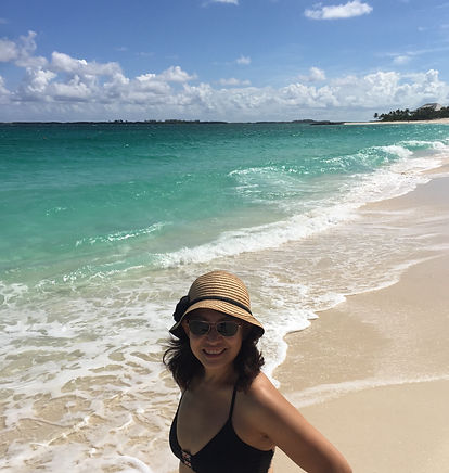 girl, wearing sunglasses and a beach hat, standing on the beach