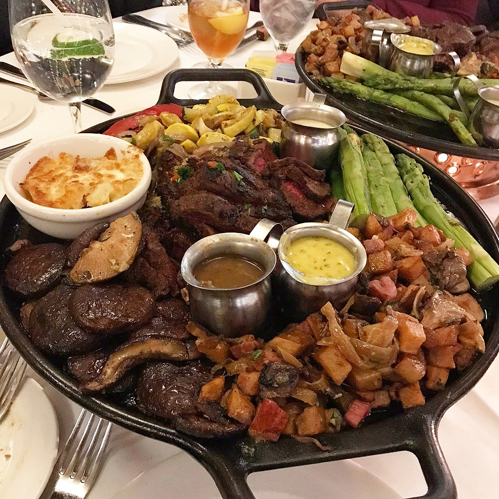 platter of steak with mushrooms, vegetables, and sauces