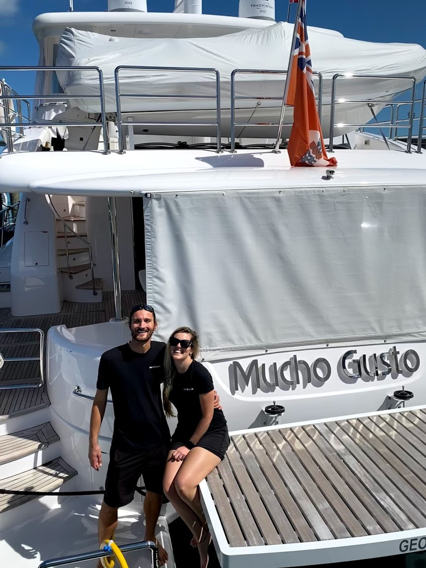 Man and woman on yacht named Mucho Gusto