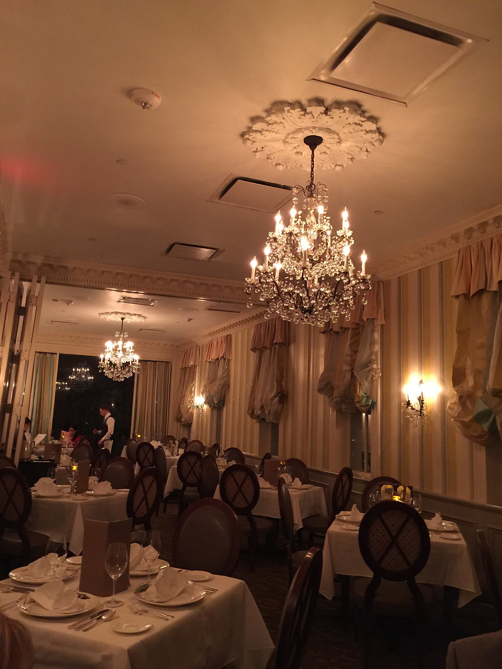elegant dining room with tables, chandeliers, and light sconces