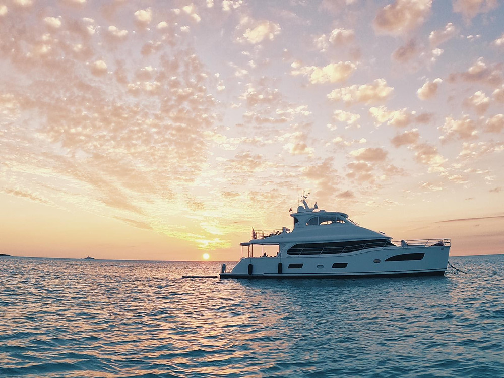 Yacht on calm ocean with sunset in the background