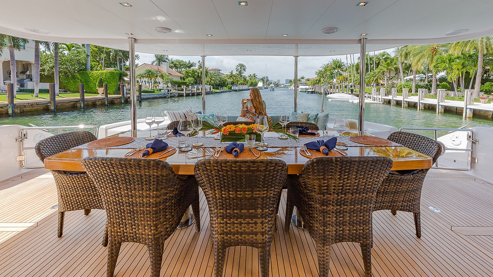Woman behind dining table on aft of luxury yacht