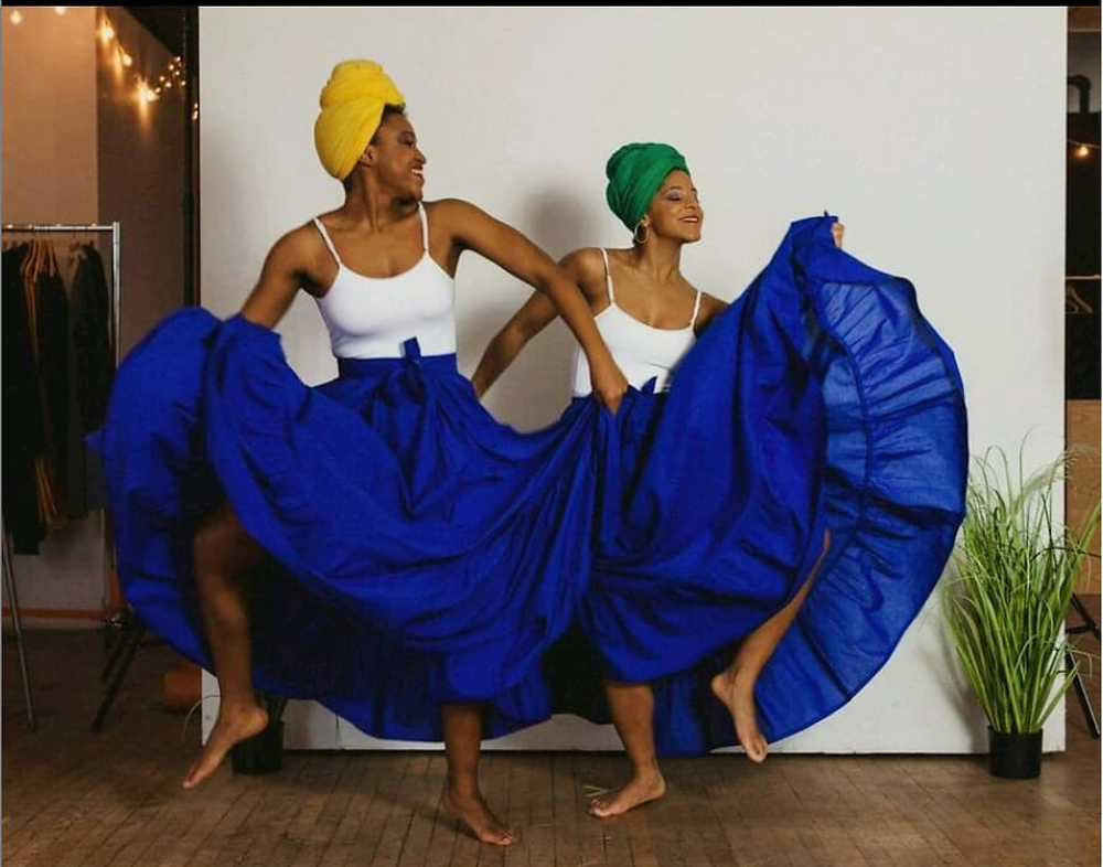 Two dancing African-American women in white tops and blue skirts.
