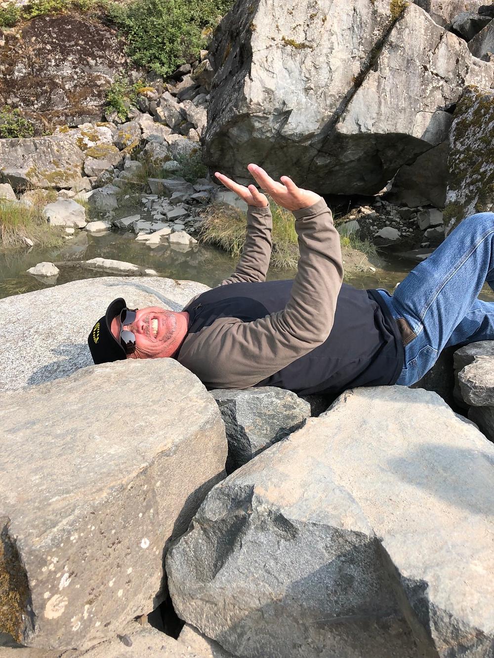 Man pretending to be pushing off a boulder