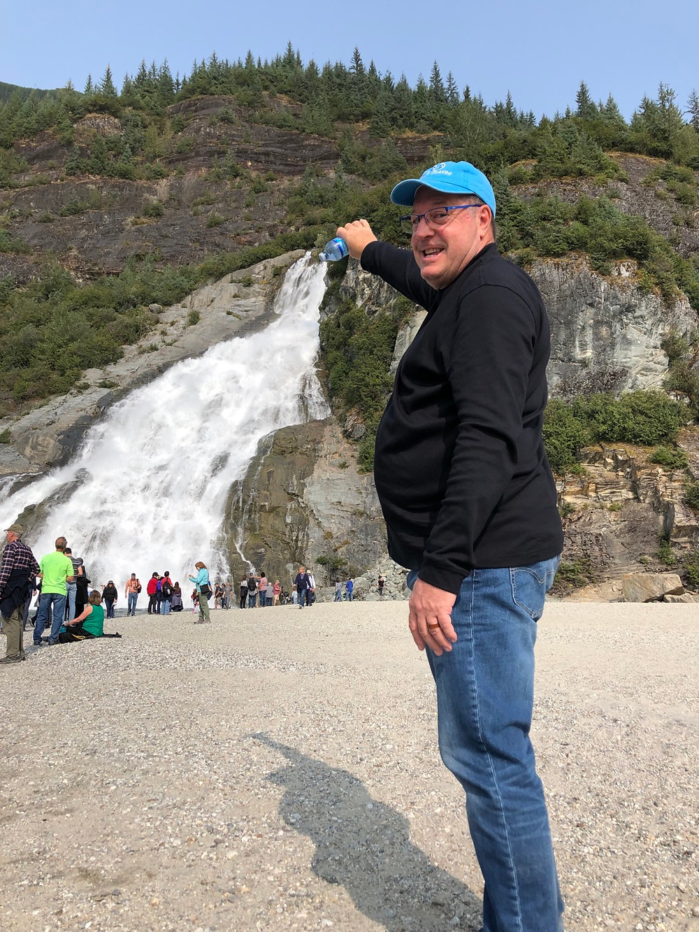 Man pretending to be emptying his water bottle but he is standing near a waterfall