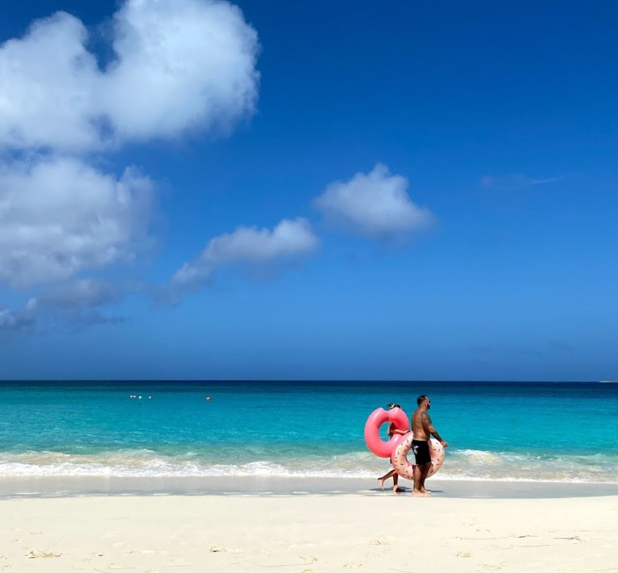 couple walking on the beach, carrying floating devices