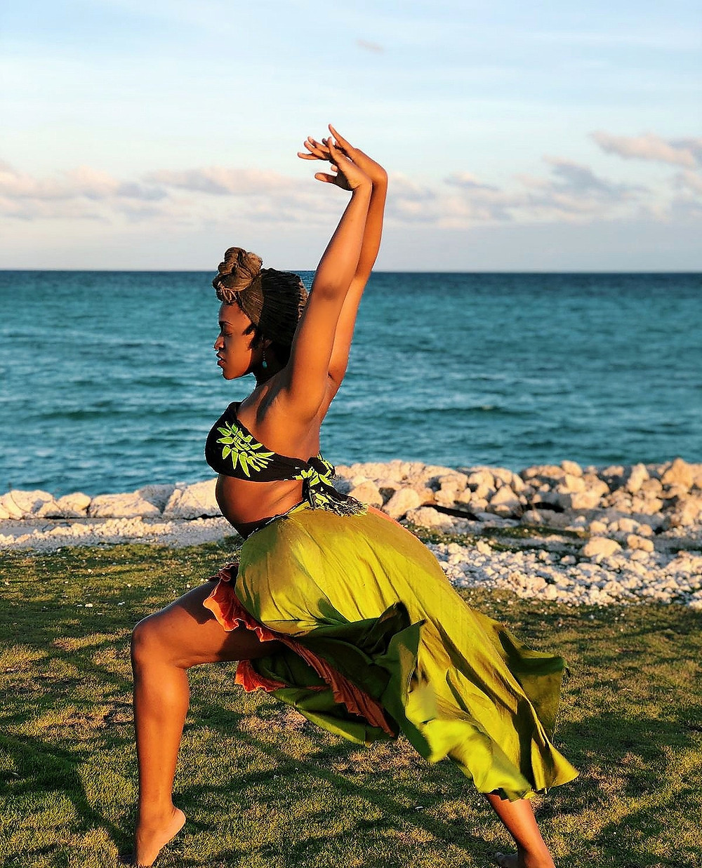 Bahamian woman in a dance pose, arms raised and hands flexed