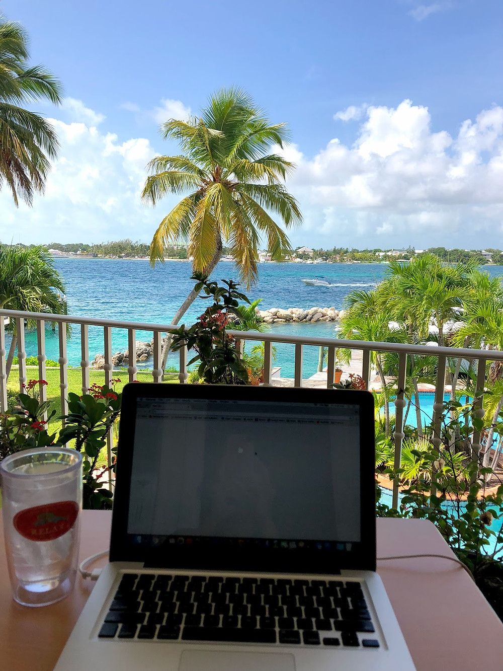 laptop and drink tumbler on a table at a balcony overlooking a palm tree and the ocean