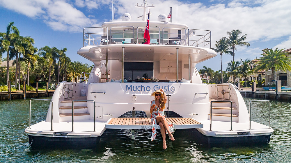 Hat-wearing woman sitting on the stern of a yacht named Mucho Gusto