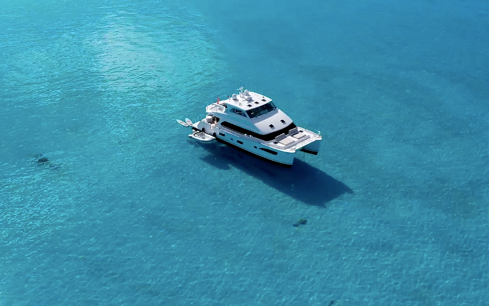 A luxury catamaran cruising on clear blue waters.