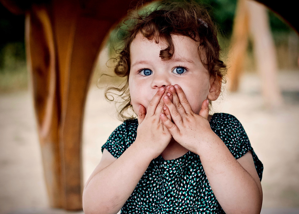 Petite fille se tenant la bouche pour ne pas parler