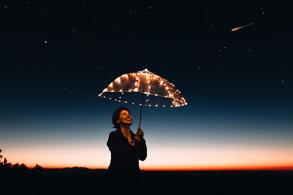 Femme portant un parapluie lumineux dans la nuit