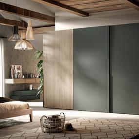 A sliding wardrobe in matt lacquer and wood veneer