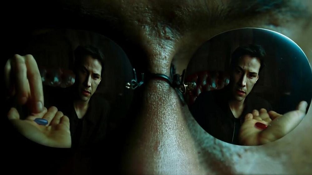 Dans Matrix, Neo prend la pilule rouge pour sortir de la matrice et commencer sa quête initiatique d'élu. // Source : The Matrix, film (1999)