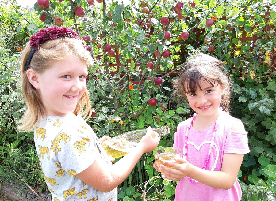 Girls pour freshly pressed apple juice from the Valley Project community apple press day