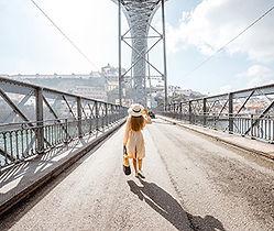 Frau, mit Hut, die in sommerlicher Atmosphäre auf einer Brücke geht - von hinten betrachtet