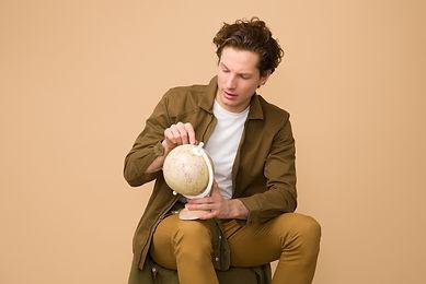 man-sitting-holding-white-desk-globe-103