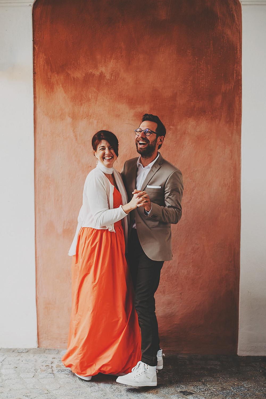 fröhliches Brautpaar, Hochzeit im Kloster Seeon, orange Wand, Brautpaar tanzt