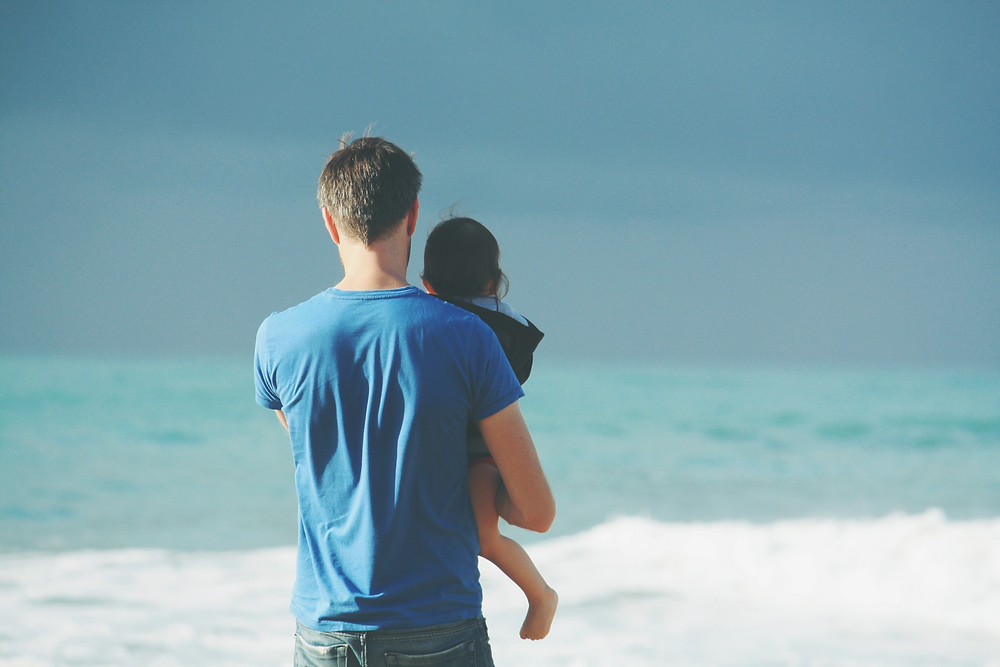 Father holding his toddler in his arms on a beach, while looking out at the turquoise sea.
