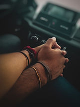 People holding hands in a car
