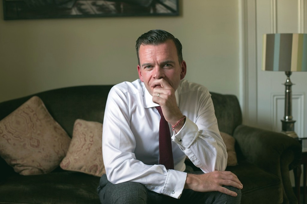 Dr Paul D'Alton looking pensive on the couch in his living room.