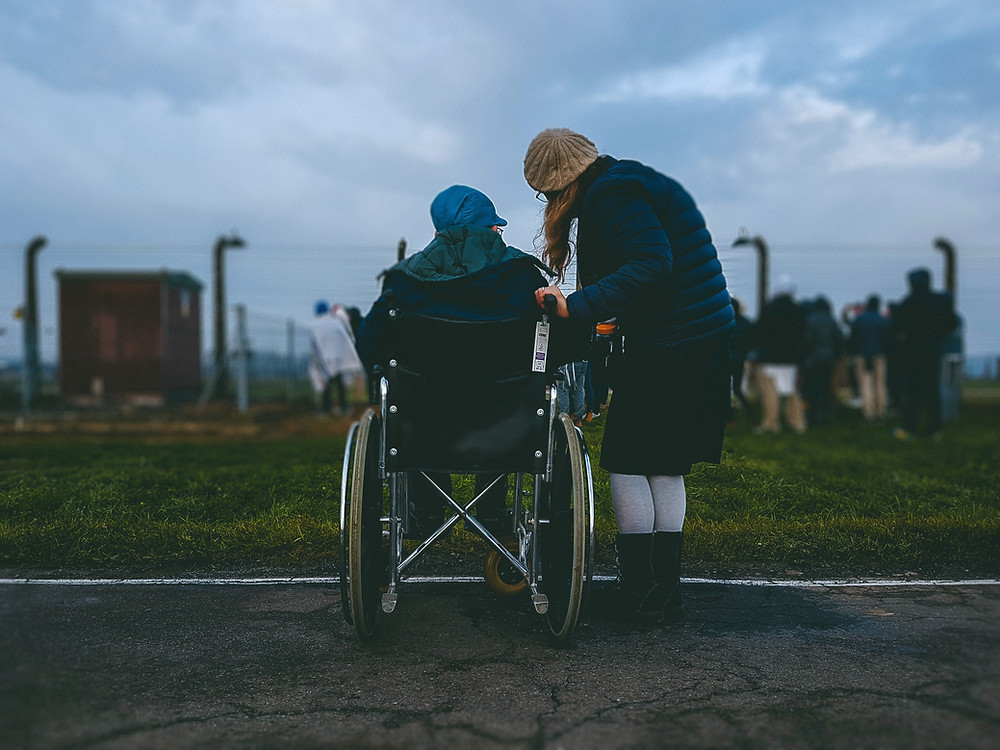 Mother leaning down and talking to son (in wheelchair) in a field.