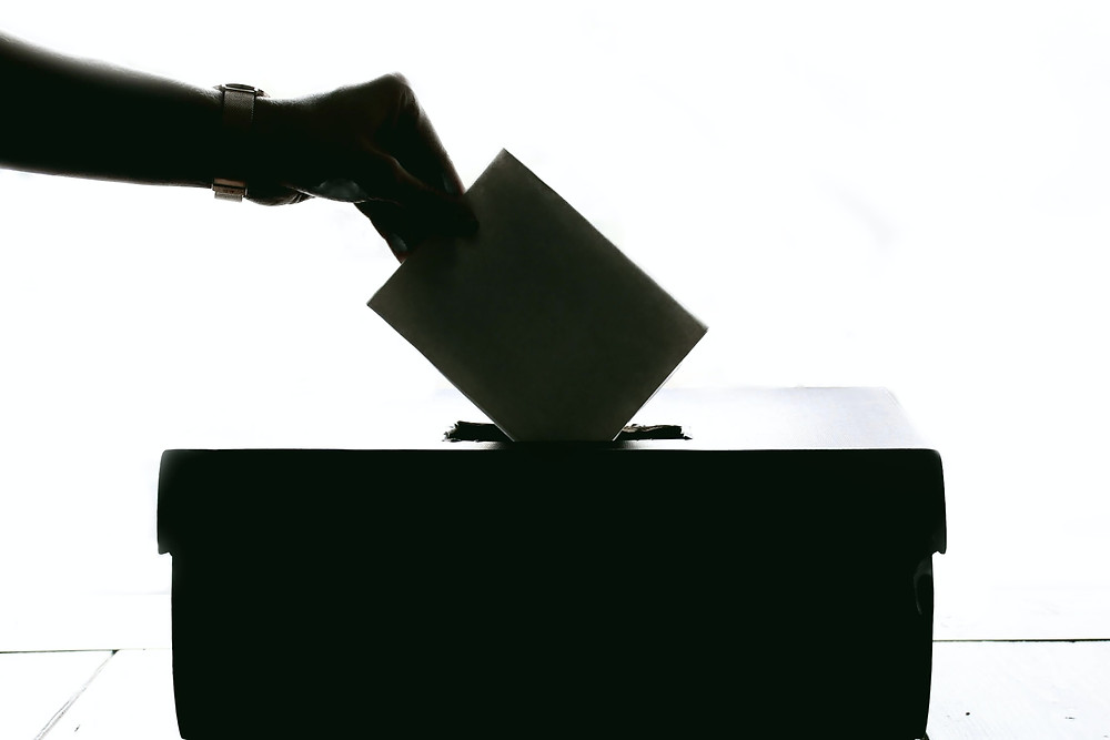 Vote being cast into a ballot box.