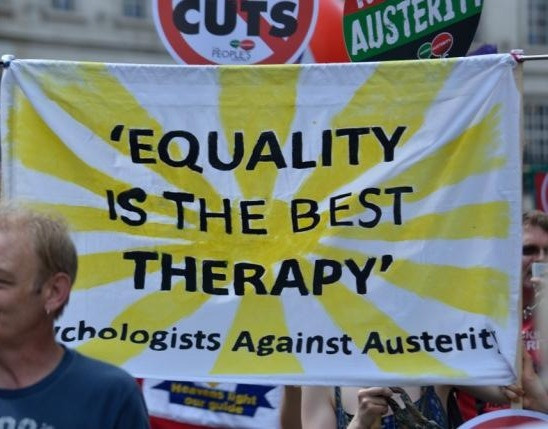 Sign from an austerity protest which reads 'Equality is the best therapy. Psychologists against austerity.'