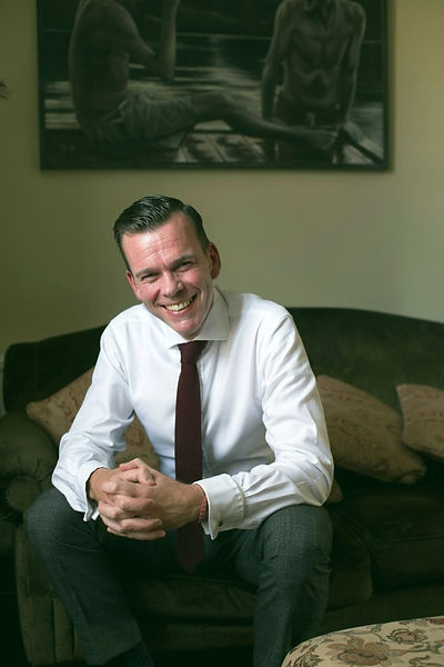 Dr Paul D'Alton smiling on his couch.