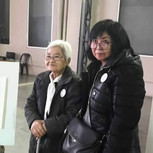 Elsa Oshiro and her mom with the portrait and chair of Jorge Oshiro.