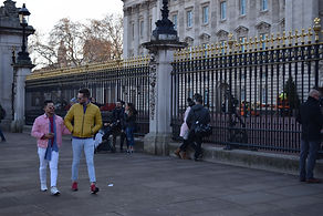 A couple walks infront of Buckingham Palace