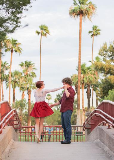 Young couple engagement photography dancing on bridge