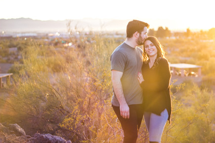 young couple engagement photography desert kiss