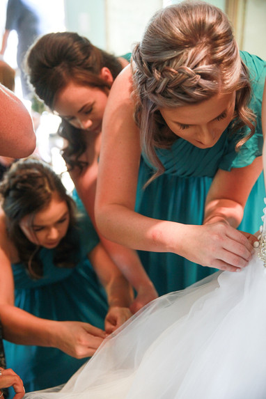 Bride getting ready with bridesmaids putting wedding dress on